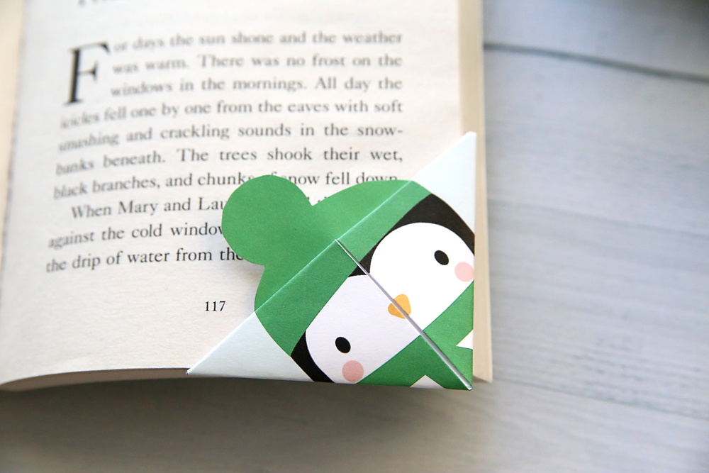 Penguin corner bookmark on a book
