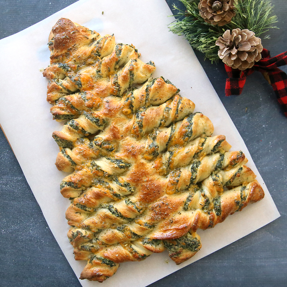 Breadsticks in the shape of a Christmas tree filled with spinach dip