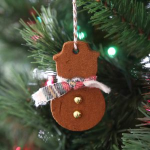 Cinnamon ornament in the shape of a snowman hanging on a Christmas tree