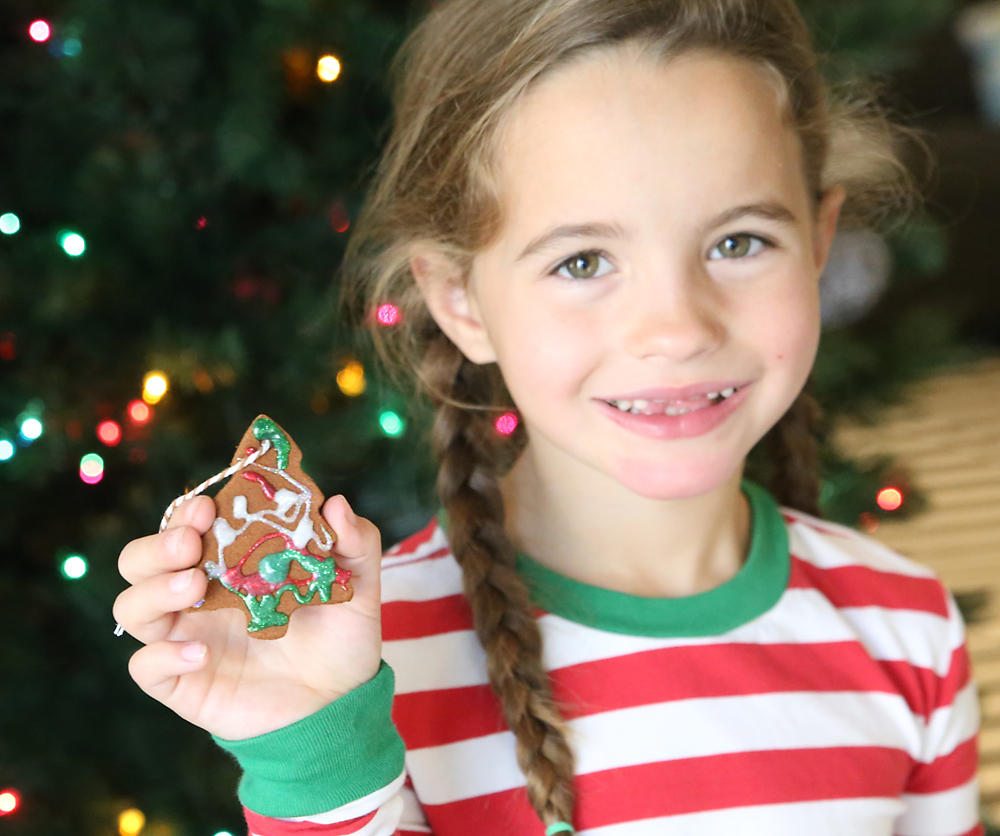 Girl with homemade cinnamon ornament decorated with glitter glue.