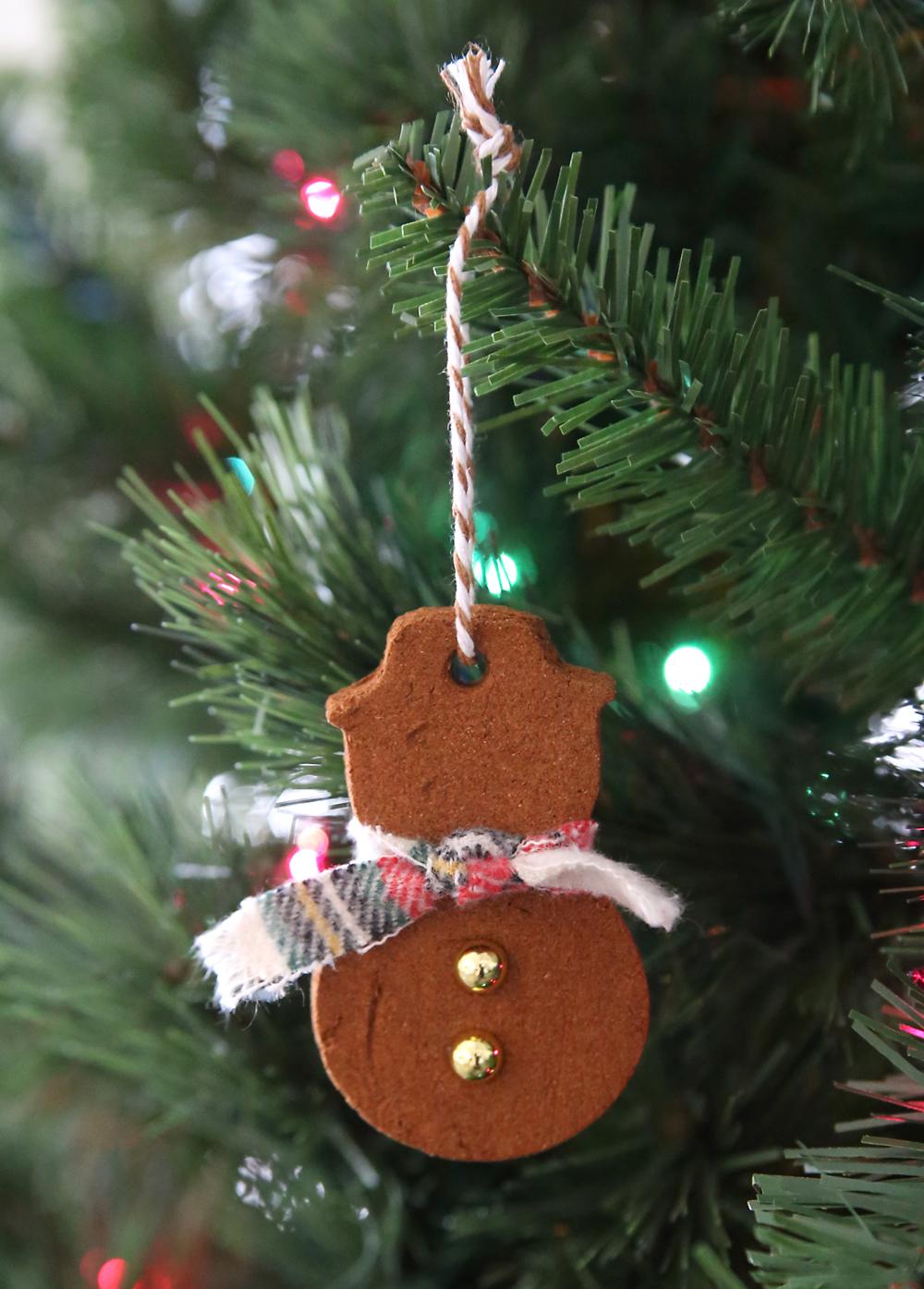 Snowman cinnamon ornament hanging on a Christmas tree.