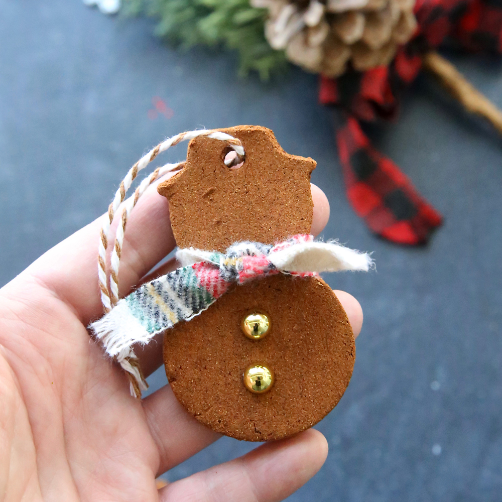 Hand holding a cinnamon Christmas ornament in the shape of a snowman
