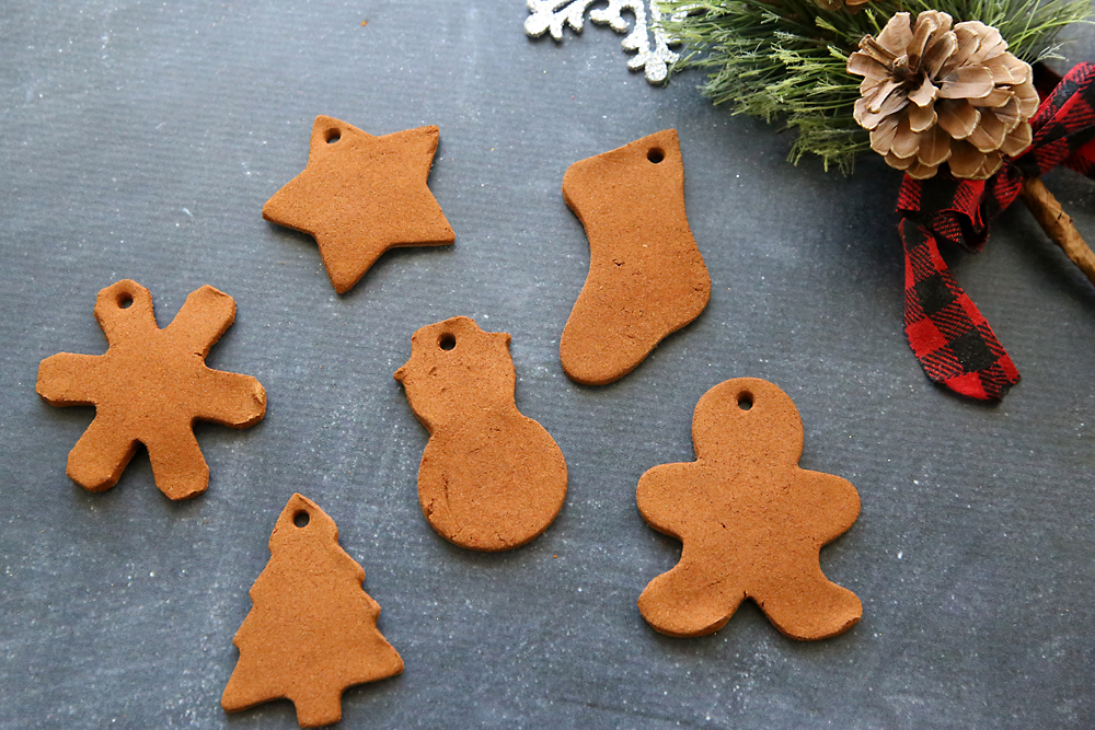 6 cinnamon ornaments on a table: snowflake, star, stocking, tree, and gingerbread man shapes