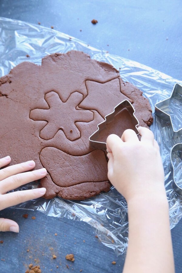 Hand using cookies cutters to cut Christmas shapes from cinnamon applesauce dough