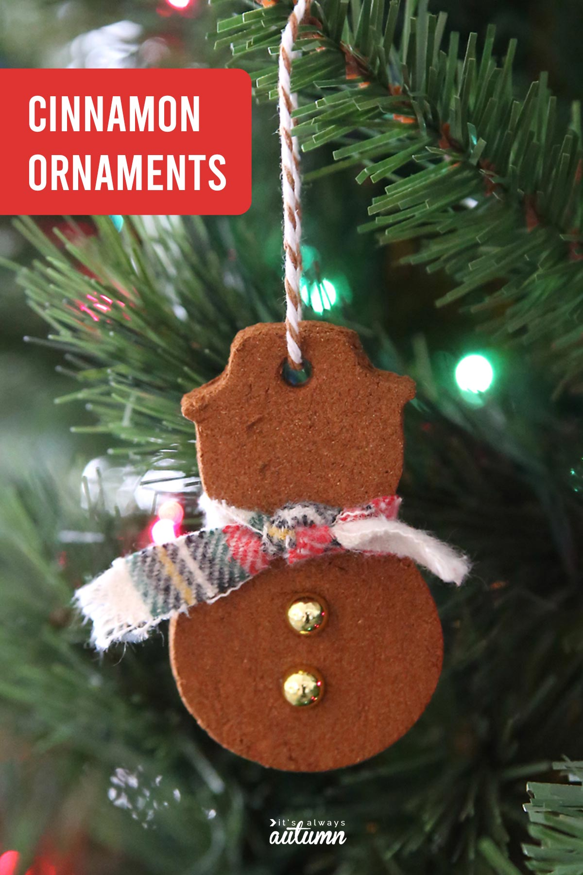 Homemade cinnamon ornament in the shape of a snowman hanging on a Christmas tree