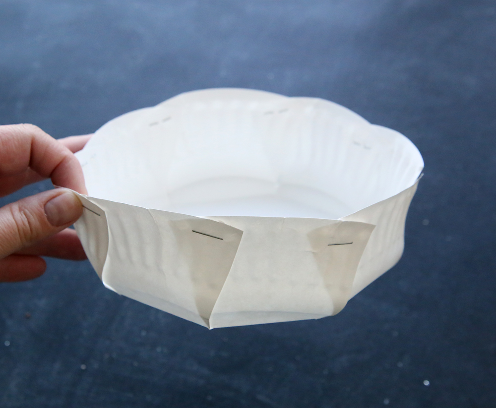 Hand holding paper plate that has been cut and sides folded up and stapled to make a basket