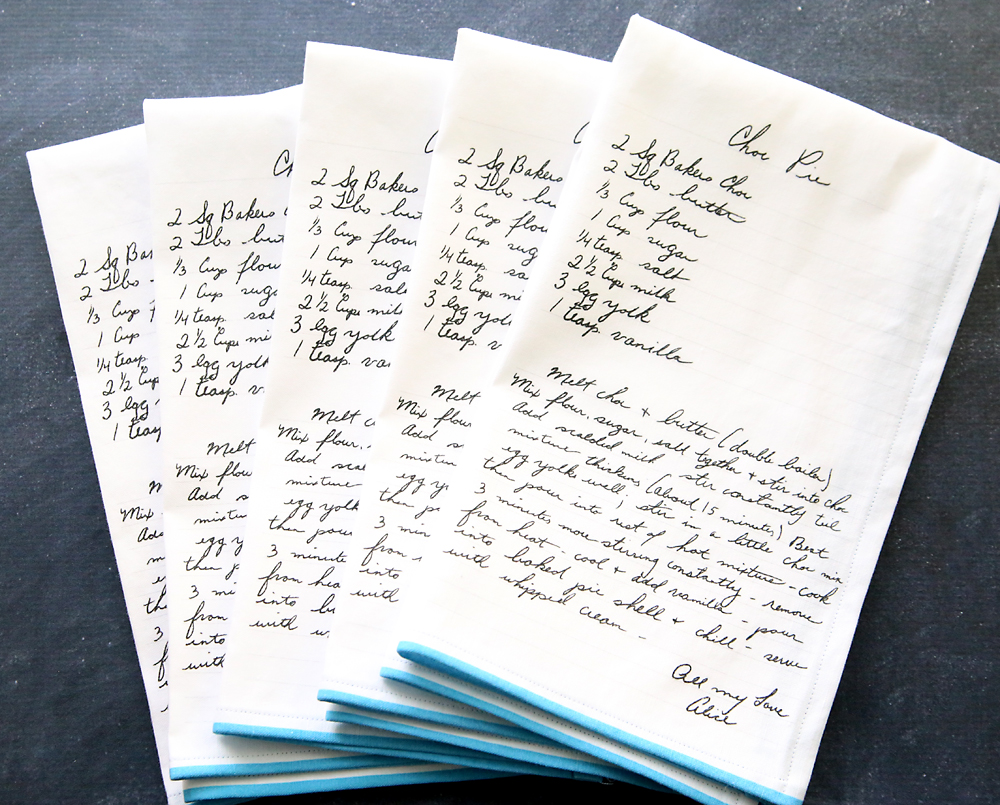 Stack of kitchen towels which have all had a handwritten recipe printed on them
