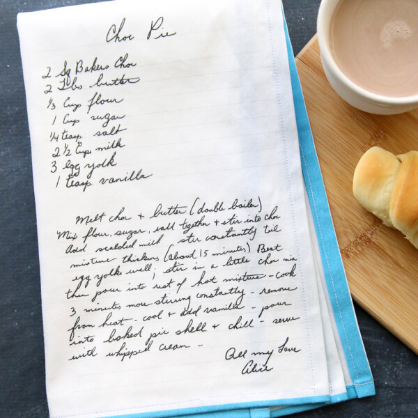 Kitchen tea towel with recipe printed on it, next to a cup of cocoa