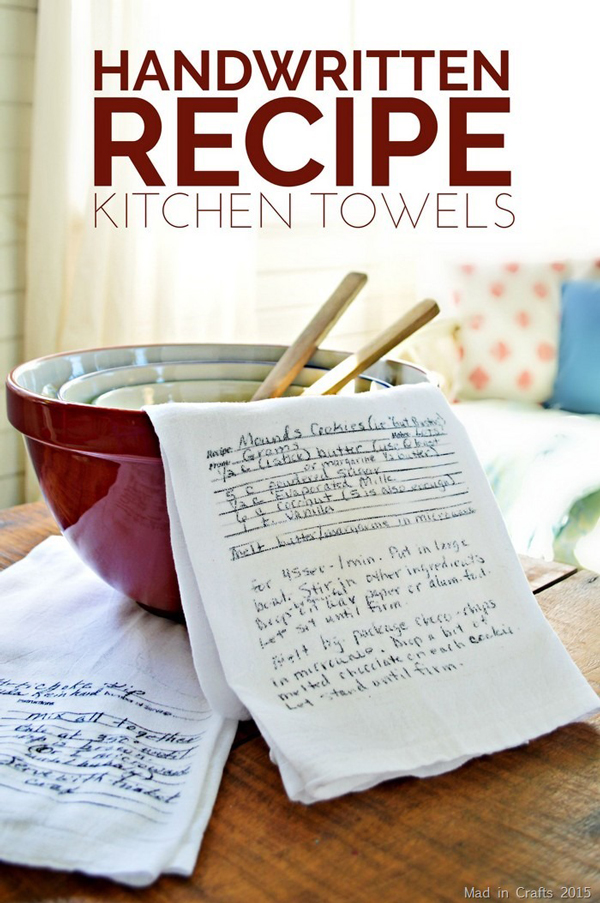 Kitchen towel with handwritten recipe on it, lying on a stack of kitchen bowls and wood spoons