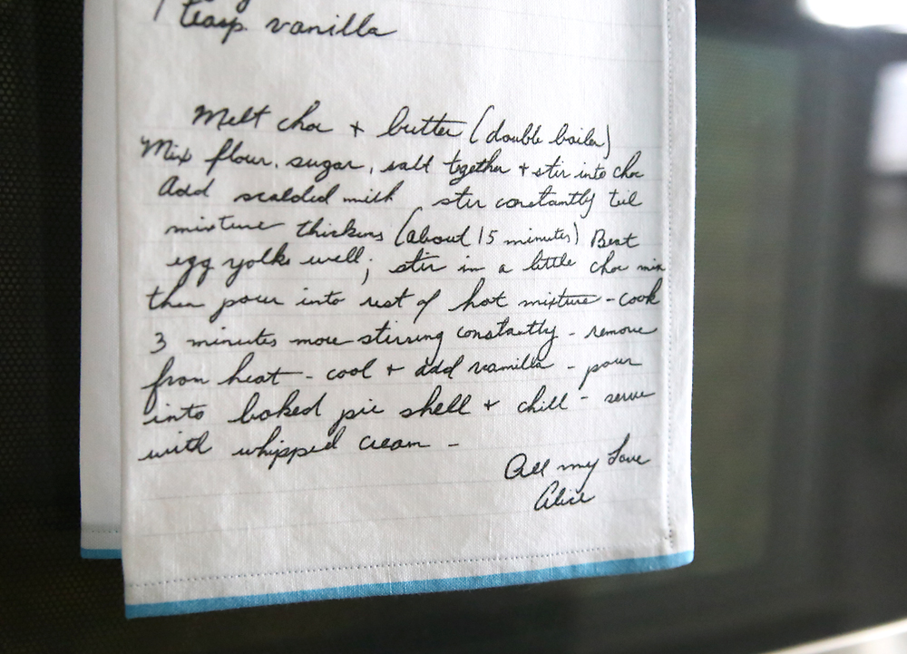 Kitchen towel with handwritten recipe on it hanging on an oven door
