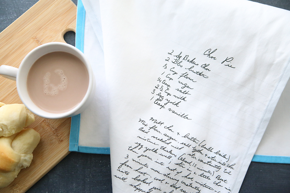 Grandma\'s handwritten recipe transferred onto a tea towel, sitting with a cup of cocoa