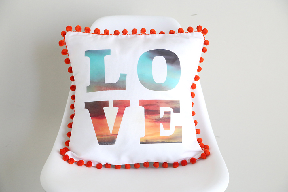 A DIY pillow with pom pom trim around the edge and the word LOVE on it, letters filled with photo of a sunset