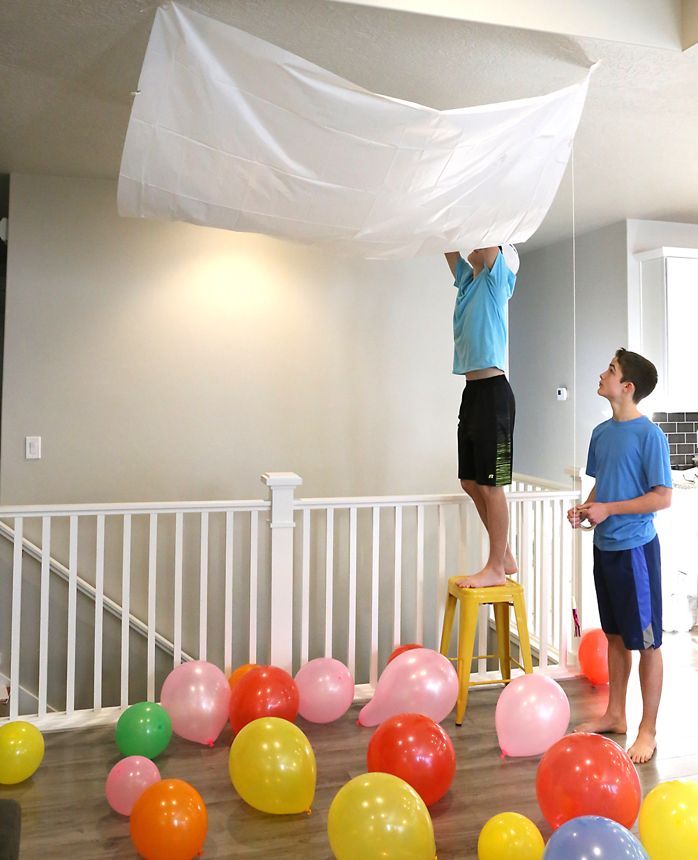 Boys taping a tarp to the ceiling to fill with balloons