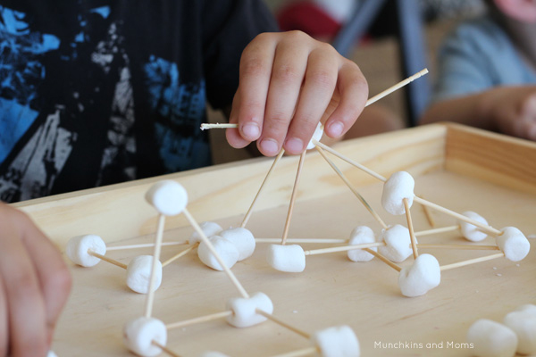 Child using marshmallows and toothpicks to build
