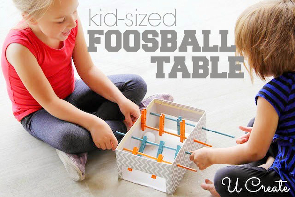 Two kids playing with a DIY foosball toy made from a cardboard box