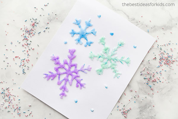 Paper with snowflakes drawn in glue, covered in salt, and painted different colors