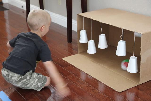 A child rolling a ball toward a cardboard box that has styrofoam cups hanging inside