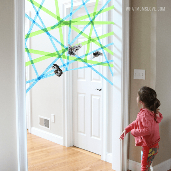 A little girl throwing paper to spiderweb made from masking tape across a doorway