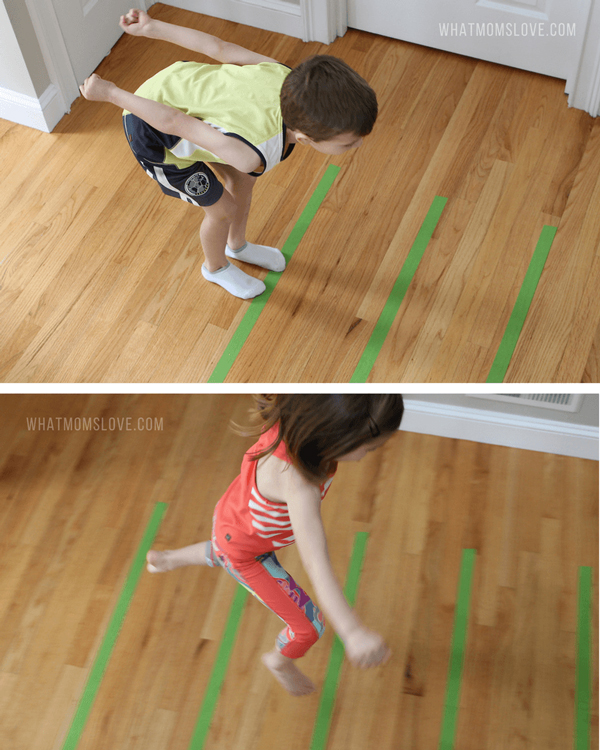 Kids jumping across lines that have been made on the floor with masking tape