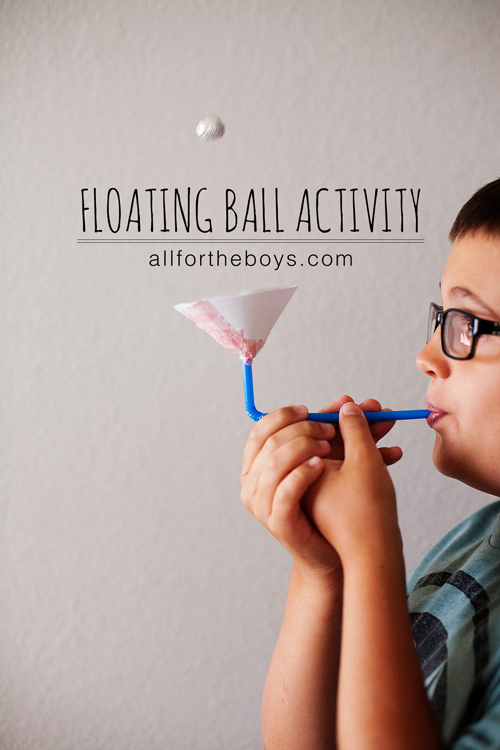 A boy blowing through a straw to make a small ball float