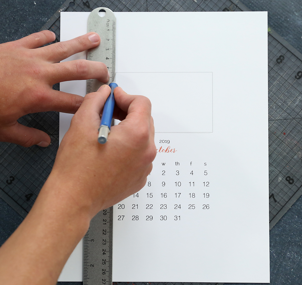 Hand using exacto knife and ruler to cut photo window out of calendar template