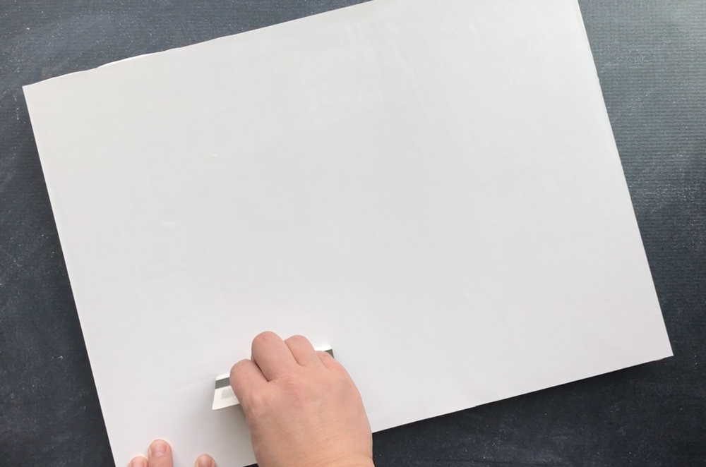 Hand using credit card to smooth photo down