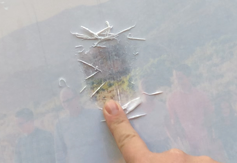 Finger rubbing wet paper fibers off gently to show picture through
