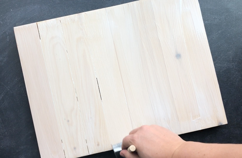 Painting mod podge on the wood pallet sign