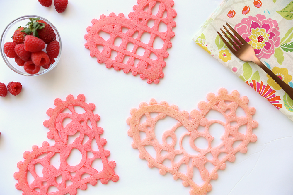 Pink pancakes in the shape of hearts that look like lace