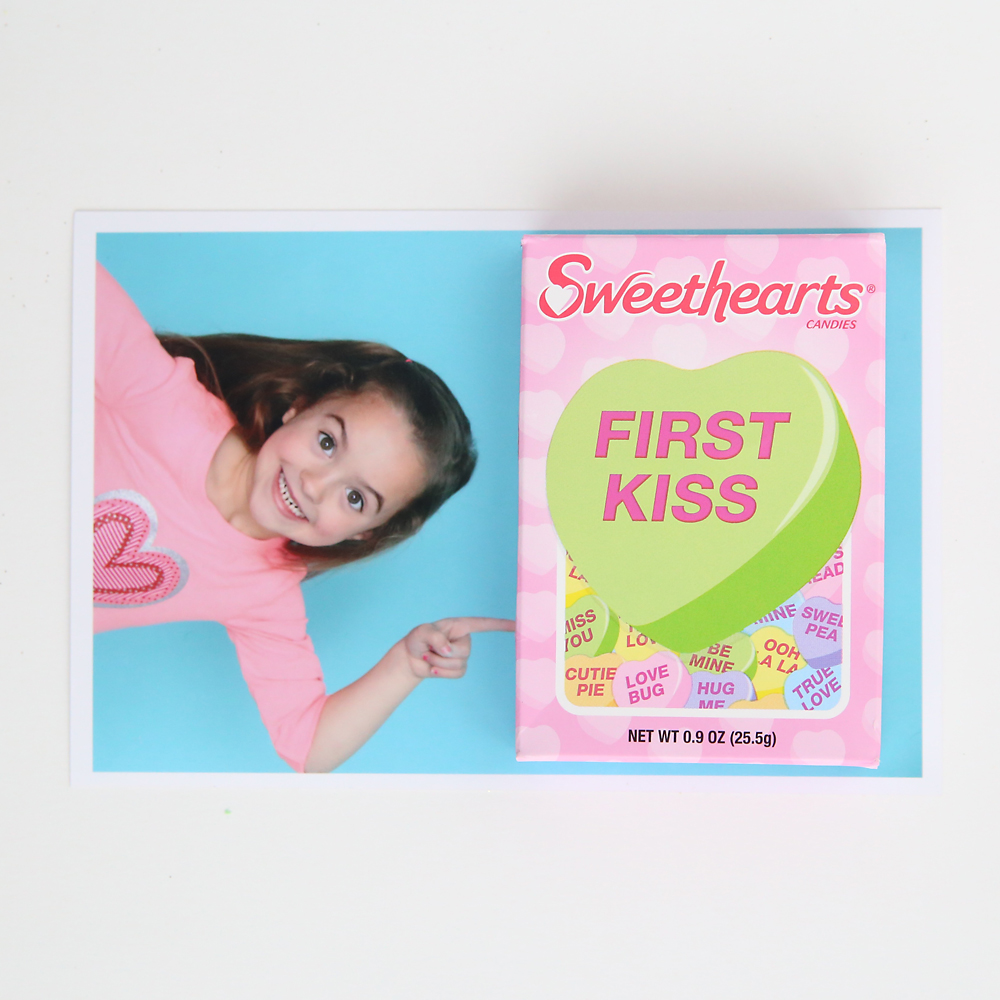 Photo of a girl pointing with a box of Sweethearts candy on top