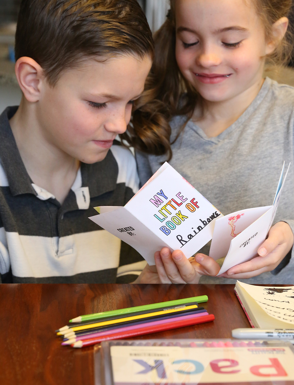 Kids look at little paper books they made