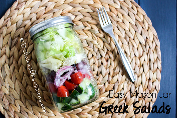 Greek salad ingredients layered in a mason jar