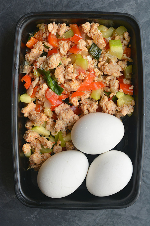 A plastic container filled with vegetable hash with eggs