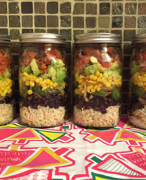 Mexican burrito bowl ingredients layered in mason juars