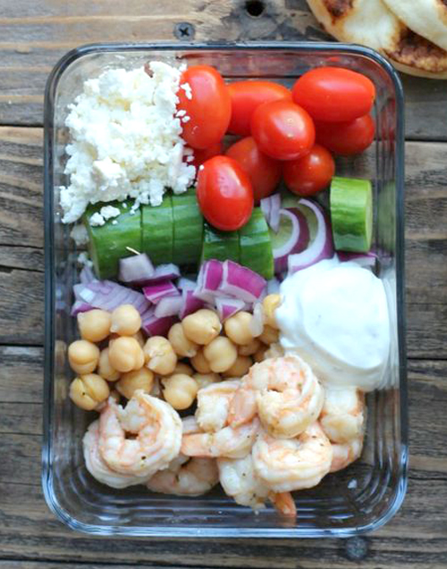 Greek shrimp meal prep bowl with vegetables, feta cheese and yogurt sauce
