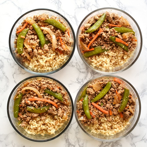 Turkey snap pea stir fry with vegetables and rice divided into meal prep containers