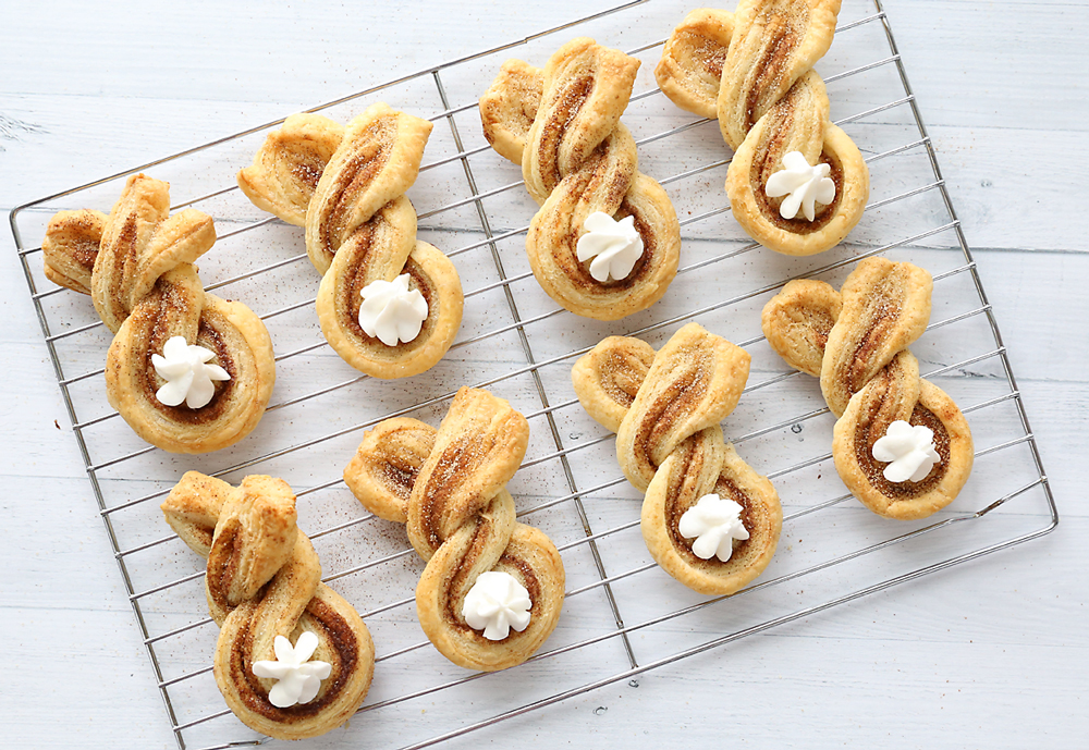 Cinnamon sugar bunny treats made from twisted strips of puff pastry with dots of whipped cream for tails