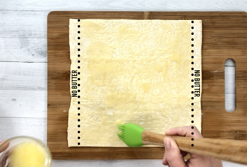 Hand brushing butter over a puff pastry sheet