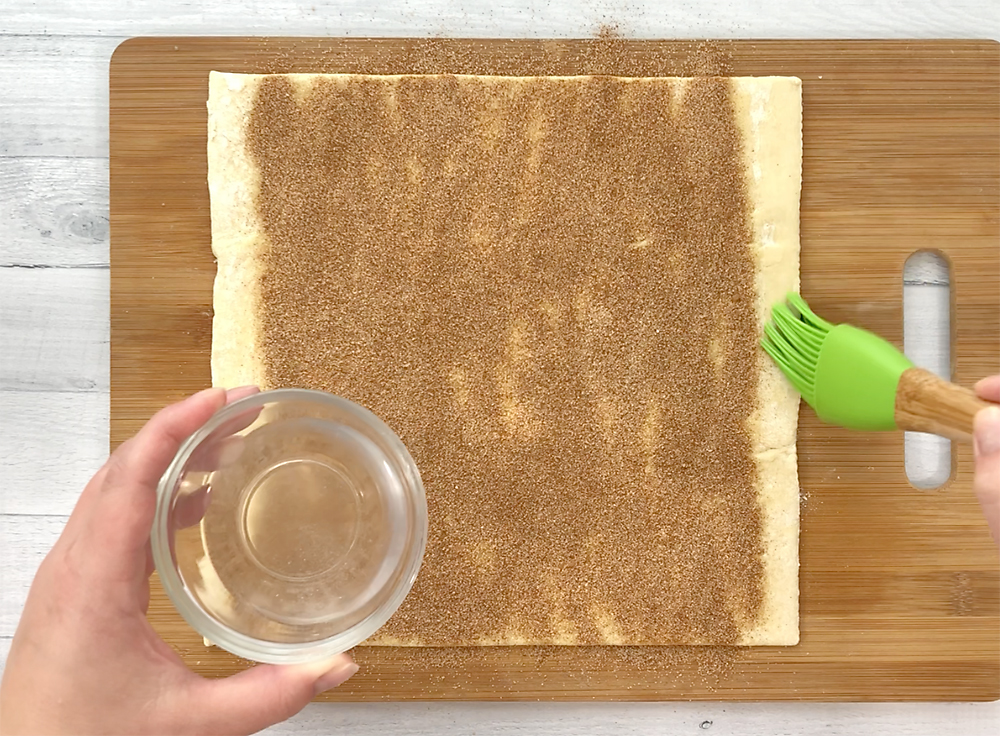 Adding cinnamon sugar over the butter on a pastry sheet
