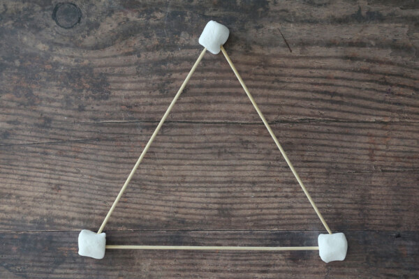 Three wood skewers connected in a triangle by marshmallows