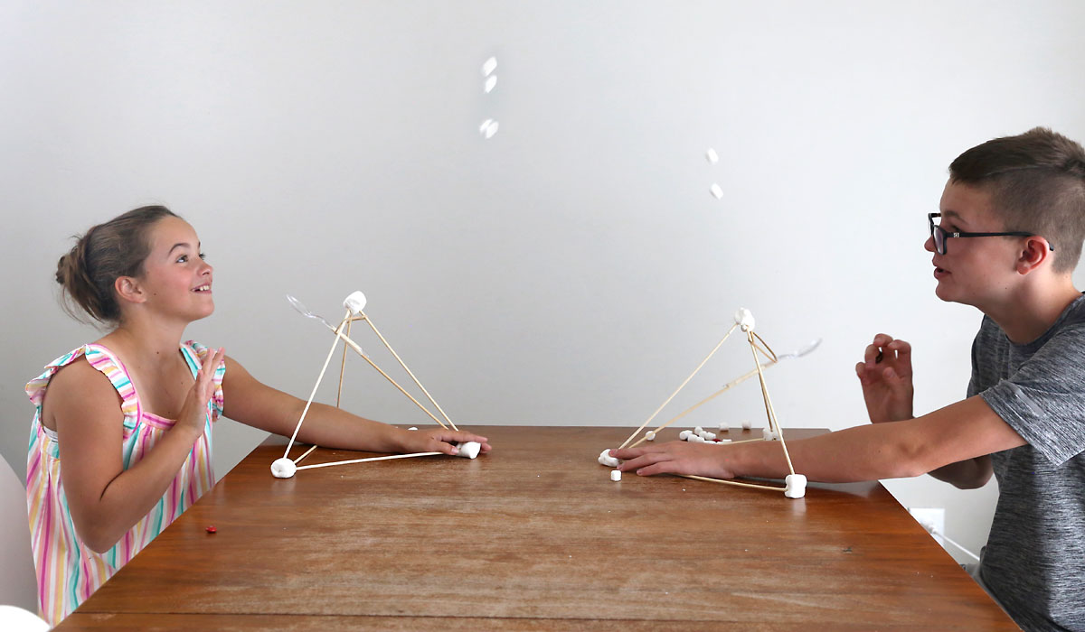 Kids launching marshmallows at each other using catapults