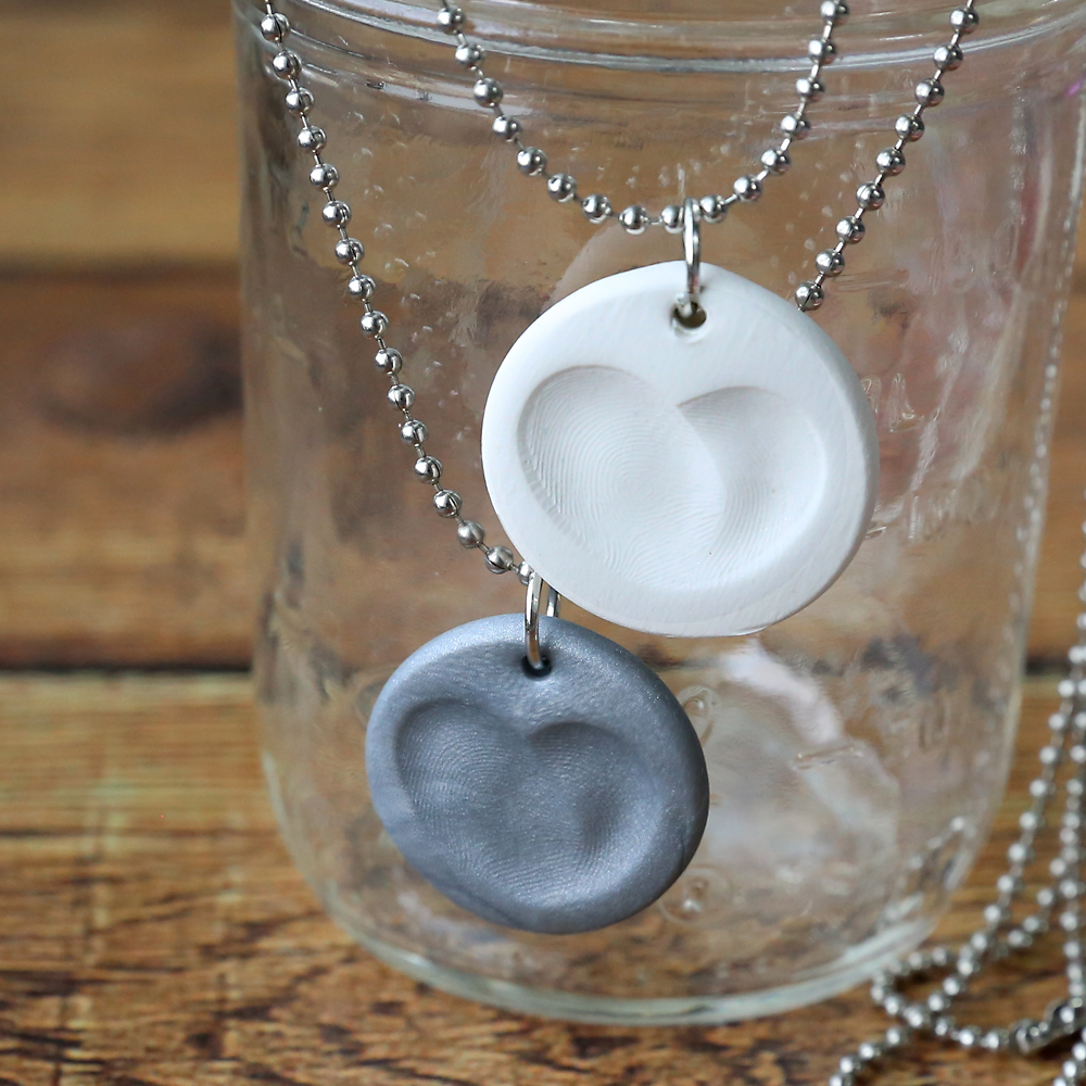 Small clay circles with fingerprints that form a heart made into necklaces
