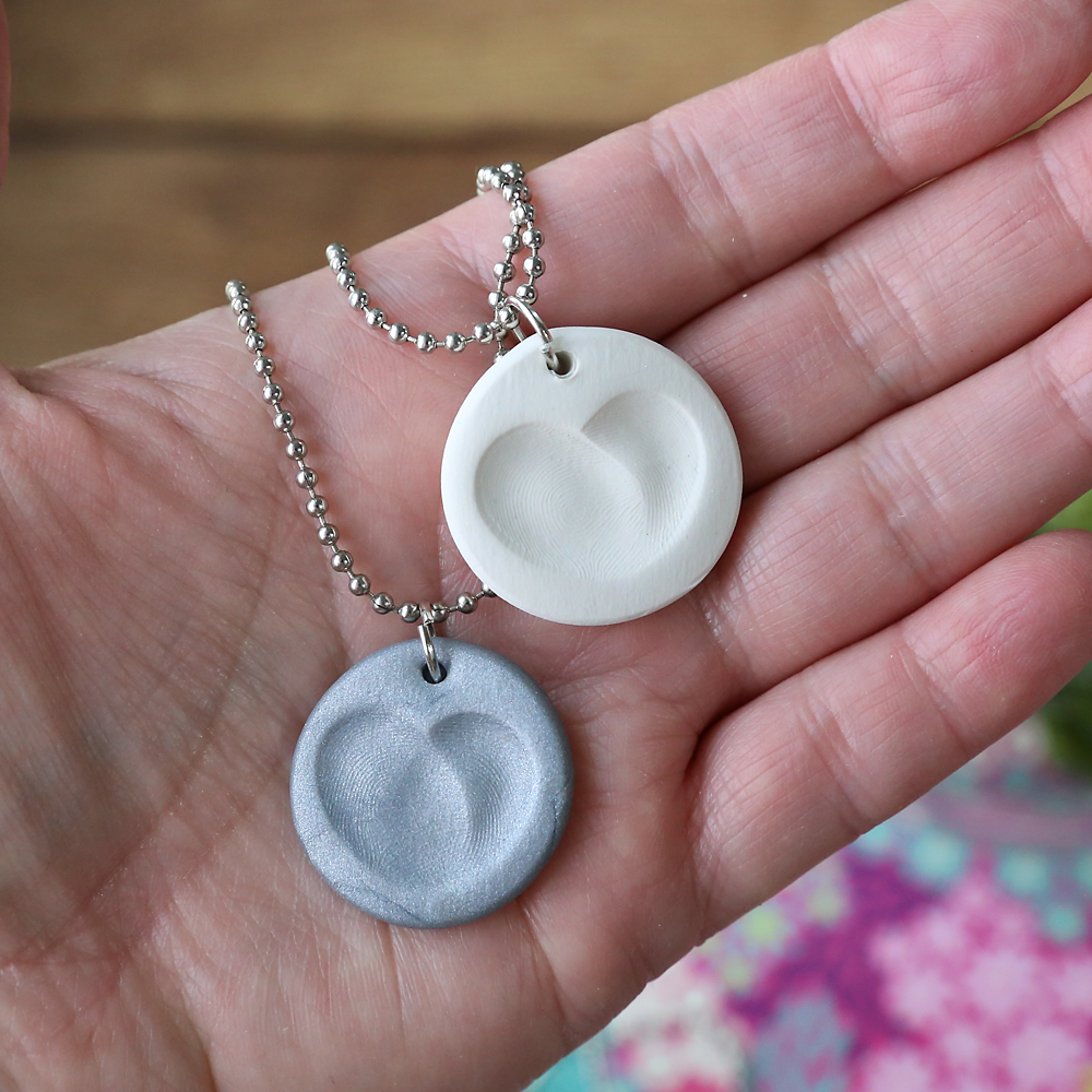 Hand holding fingerprint heart clay necklaces