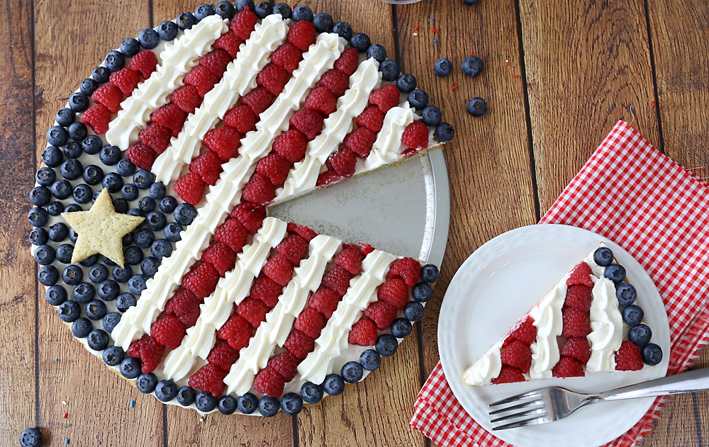 An American flag fruit pizza with one slice cut out on a plate