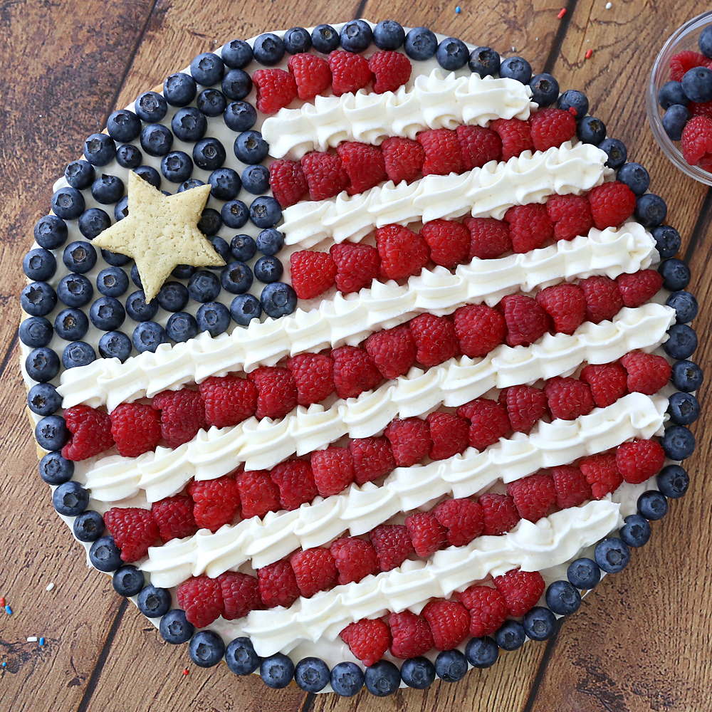 A large fruit pizza in the shape of an American flag, decorated with berries and cream