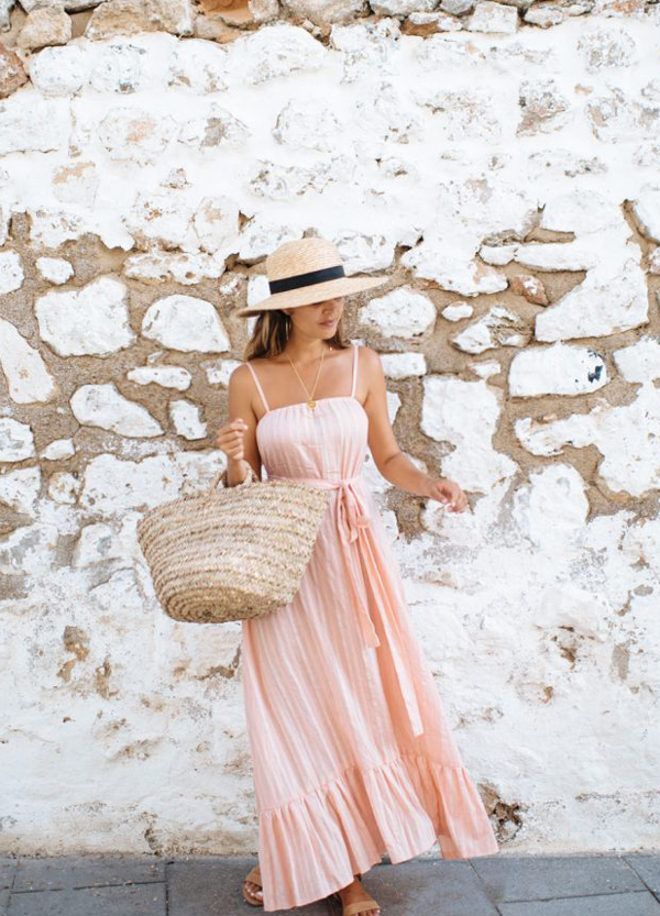 woman wearing long pink dress and hat