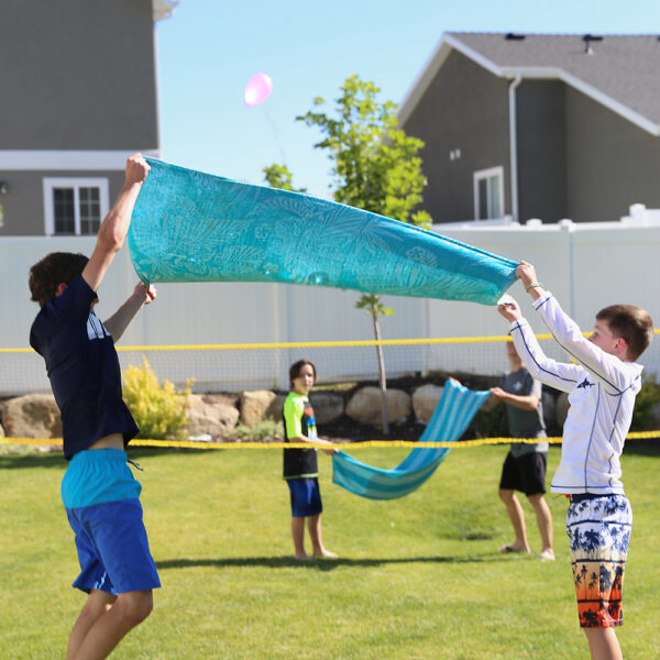 Kids playing water balloon volleyball using towels to toss water balloons