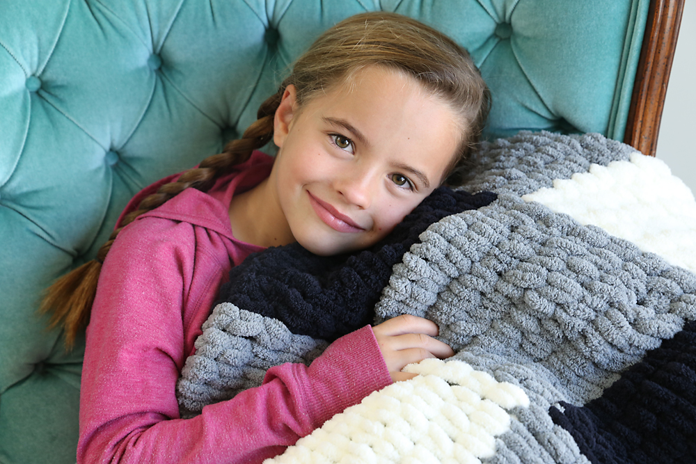 A little girl snuggling with a plaid loop yarn blanket