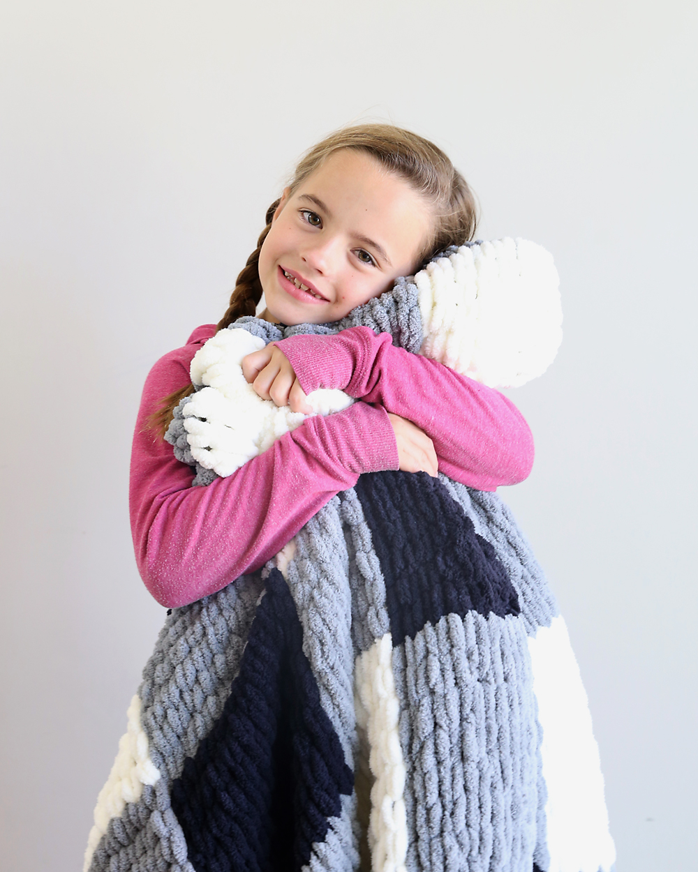 Girl snuggling with a finger knit blanket made from loop yarn