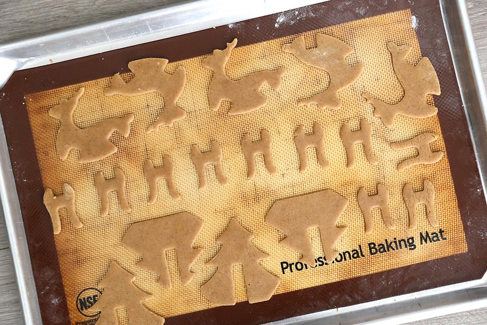 3D gingerbread cookie dough pieces on a baking sheet